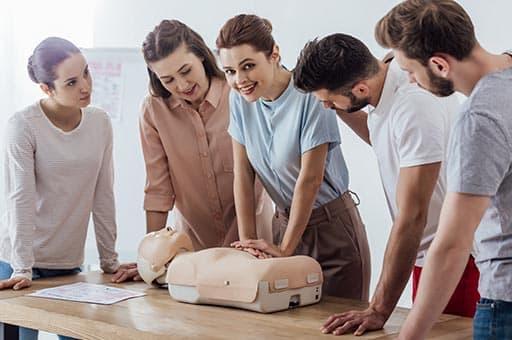 Kinderfee Erste Hilfe am Kind Kurs Teilnehmer stehen um einen Tisch. Eine Frau übt die Druckmassage.